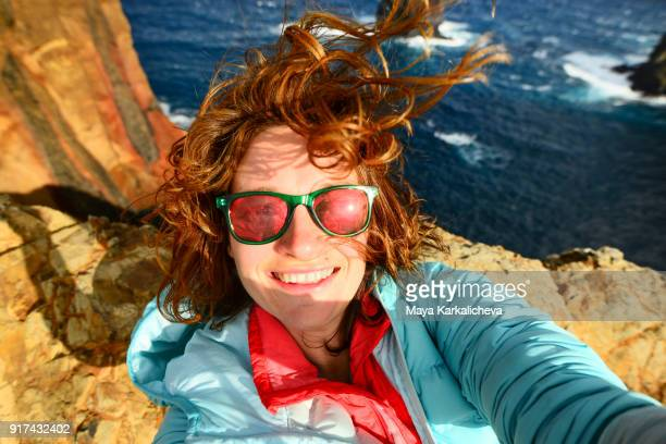 Caucasian woman with sunglasses taking selfie at Madeira island, Atlantic ocean, Portugal