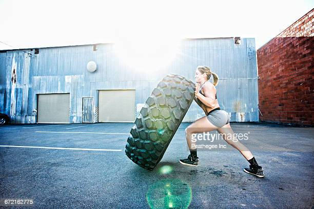 Caucasian woman working out with heavy tire outdoors