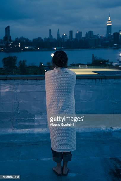 Caucasian woman wrapped in blanket admiring urban waterfront from rooftop