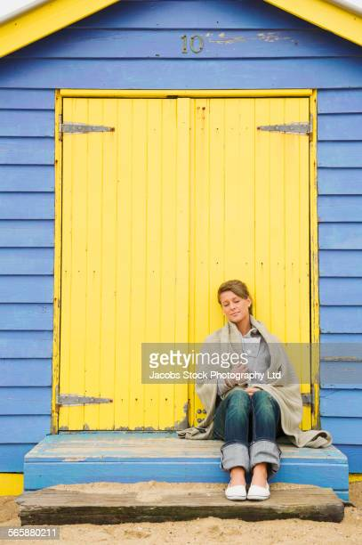 Caucasian woman wrapped in blanket on beach hut porch