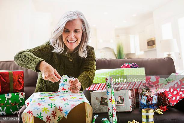 caucasian woman wrapping christmas gifts - avvolto foto e immagini stock