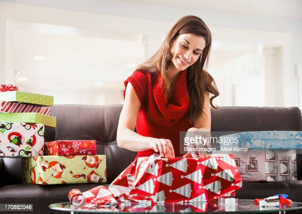 caucasian woman wrapping christmas presents in living room - avvolto foto e immagini stock