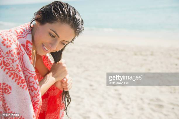 Caucasian woman wringing hair on beach