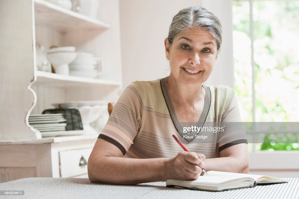 Caucasian woman writing in journal : Stock Photo