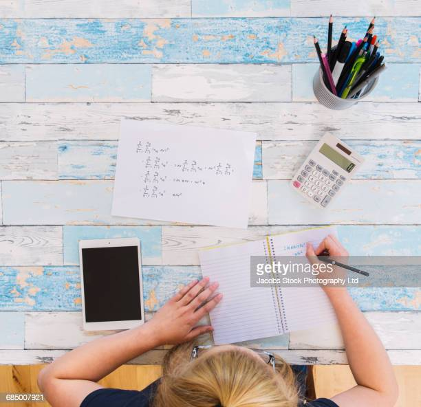 Caucasian woman writing in notebook at white wooden table