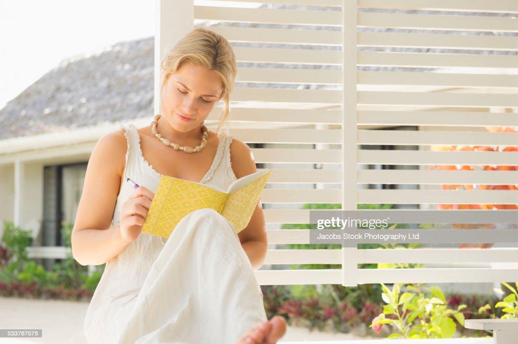 Caucasian woman writing on porch : Foto stock