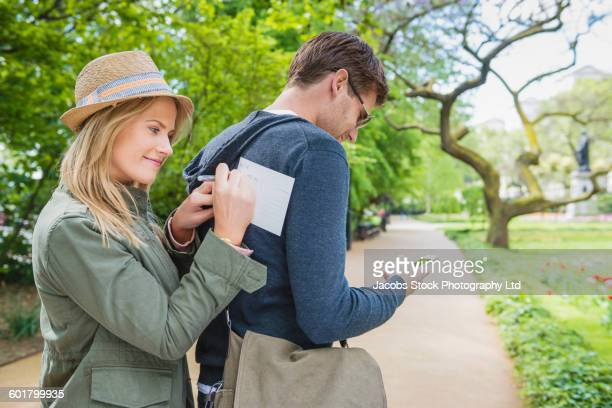 Caucasian woman writing postcard on back of boyfriend