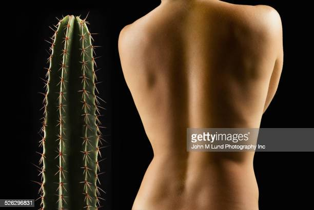 Caucasian womans bare back and cactus plant