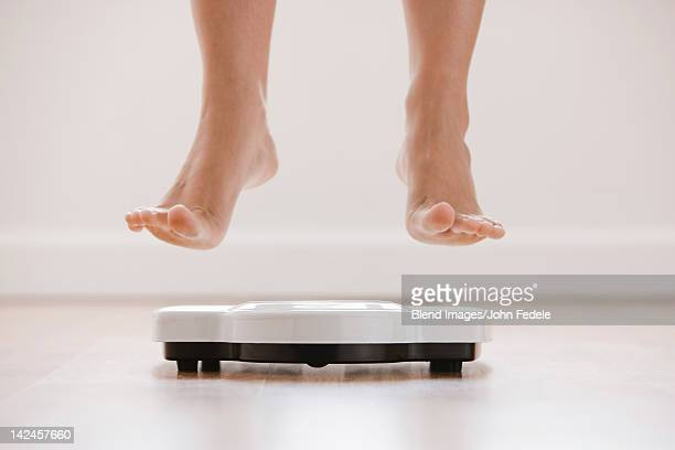 Caucasian woman's feet jumping on scale