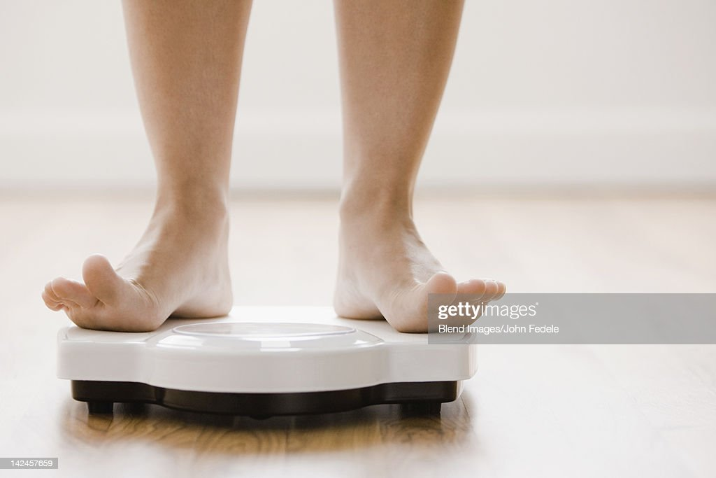 Caucasian woman's feet standing on scale : Stock Photo