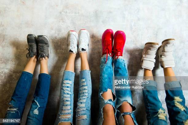 caucasian women admiring their sneakers against wall - spijkerbroek stockfoto's en -beelden