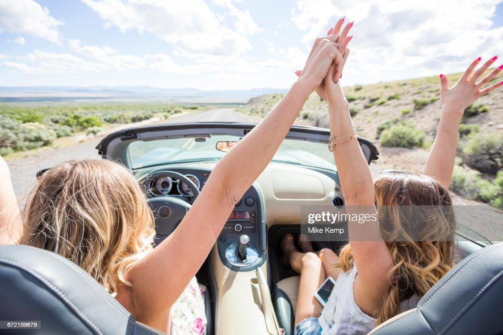 Caucasian women celebrating in sports car : Stock Photo