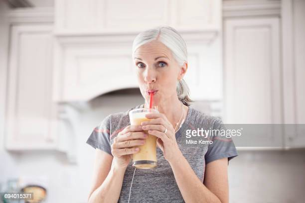 Caucasian women drinking smoothie with straw