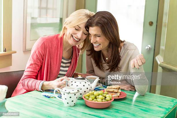 caucasian women drinking tea laughing - mid adult women stock pictures, royalty-free photos & images