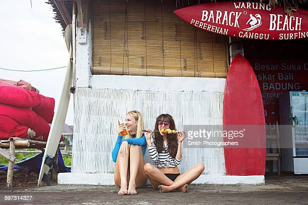 Caucasian women eating at surf hut on beach