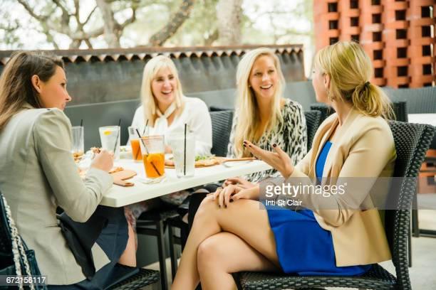 Caucasian women enjoying cocktails at bar patio