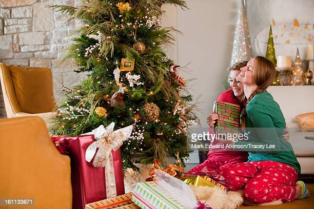 Caucasian women exchanging Christmas gifts