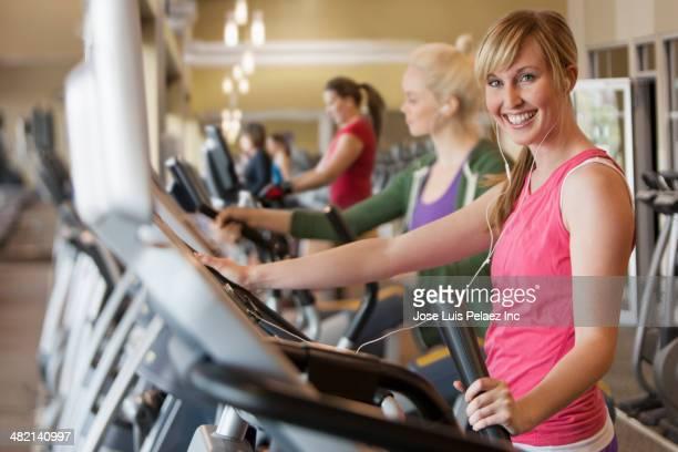 Caucasian women exercising on elliptical trainer in gym