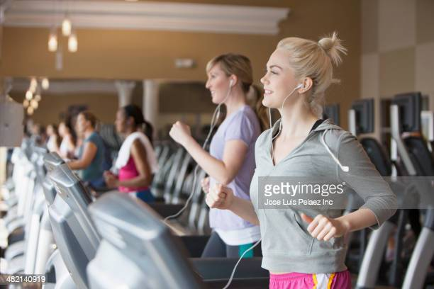 Caucasian women exercising on treadmills in gym