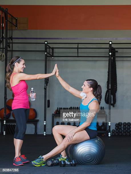 Caucasian women high fiving in gym
