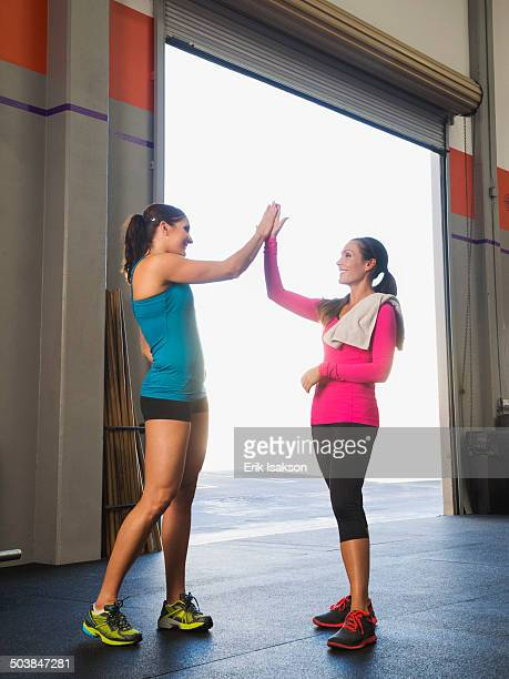 Caucasian women high fiving in gym