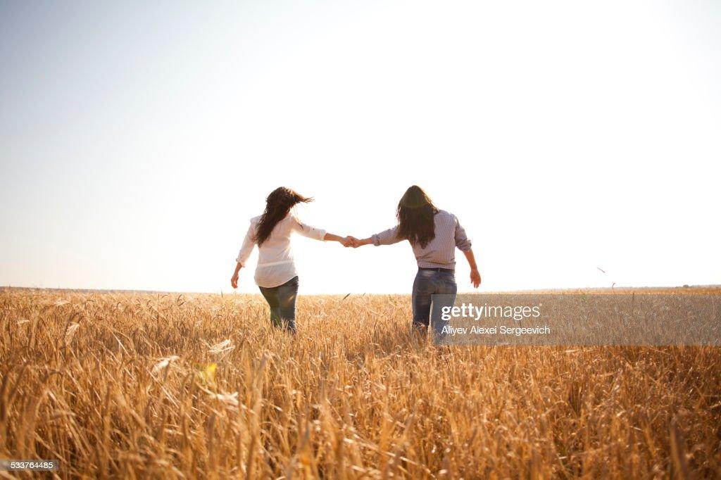 Caucasian women holding hands in rural field : Foto stock