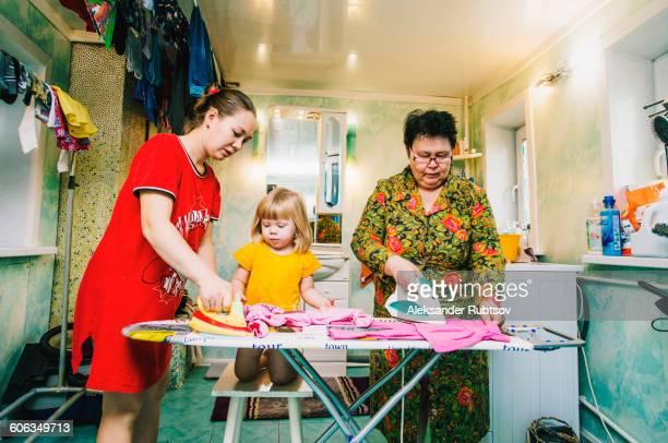 caucasian women ironing laundry - parto natural imagens e fotografias de stock