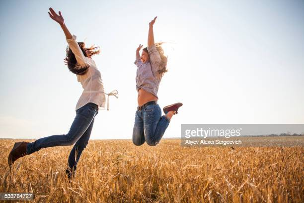 Caucasian women jumping for joy in rural field