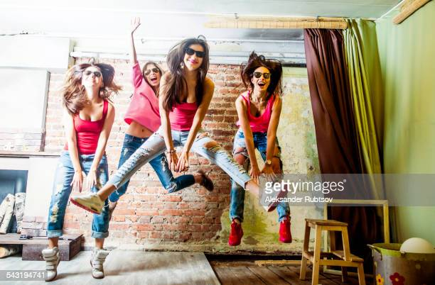 Caucasian women jumping in living room