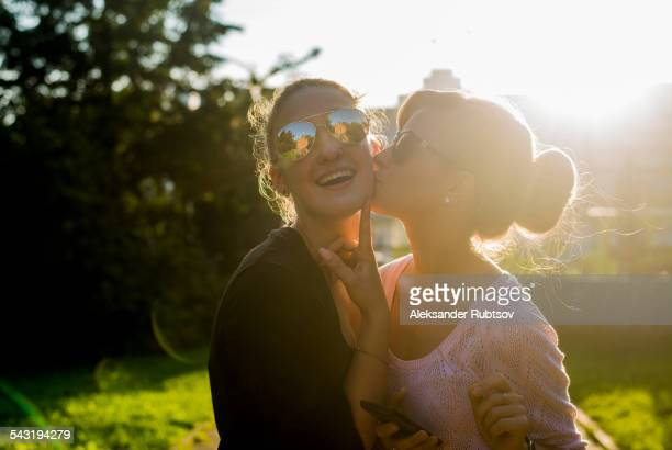 caucasian women kissing in backyard - cheek stock pictures, royalty-free photos & images
