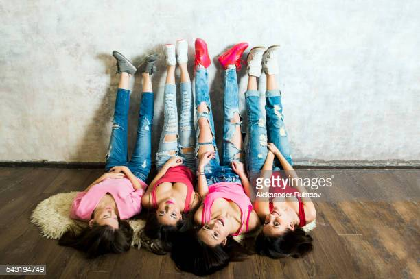 Caucasian women laying on floor with feet on wall