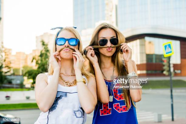 Caucasian women making faces in city