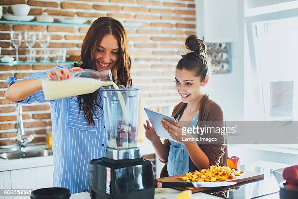 Caucasian women making smoothie in kitchen