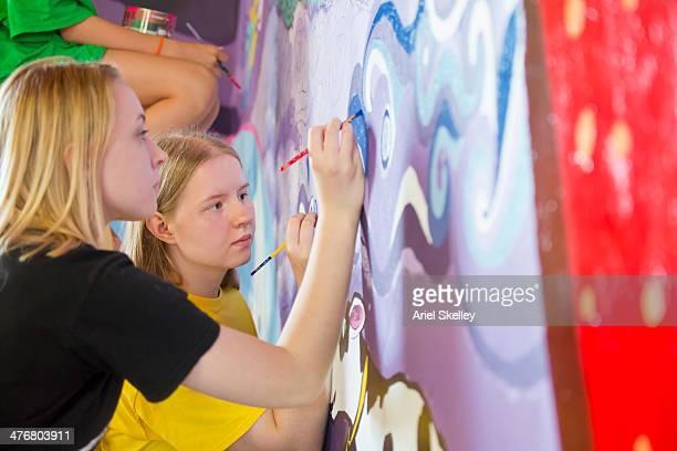 caucasian women painting mural - pintar mural fotografías e imágenes de stock