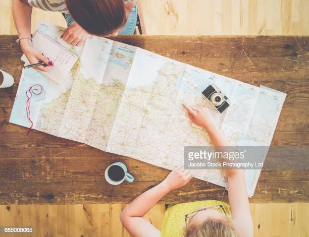 caucasian women planning trip with map on wooden table - pointing at camera stock photos and pictures