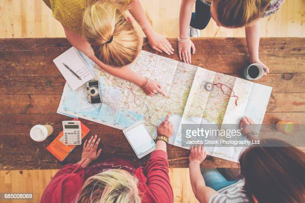 caucasian women planning trip with map on wooden table - vacaciones viajes fotografías e imágenes de stock