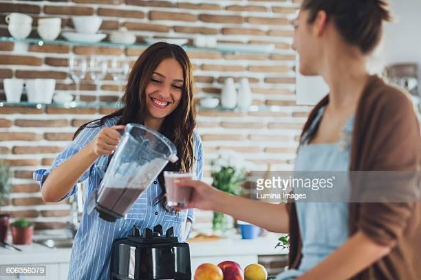 Caucasian women pouring smoothie in kitchen