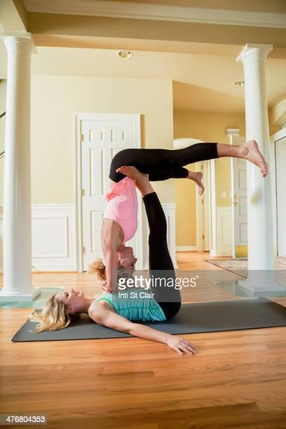Caucasian women practicing acroyoga in home