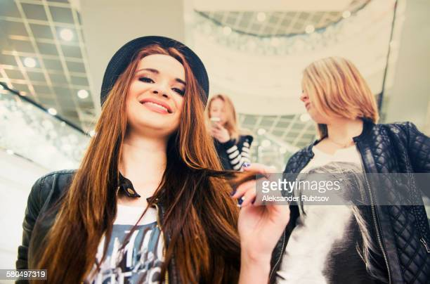 Caucasian women riding escalator in shopping mall