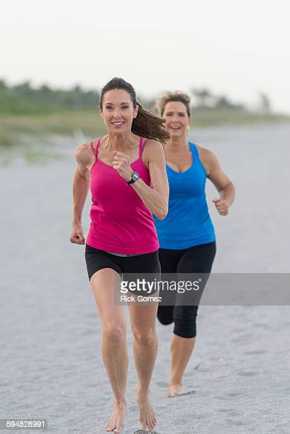 Caucasian women running on beach