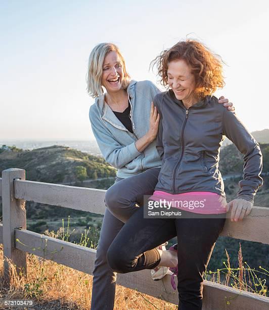 Caucasian women sitting on fence on hilltop