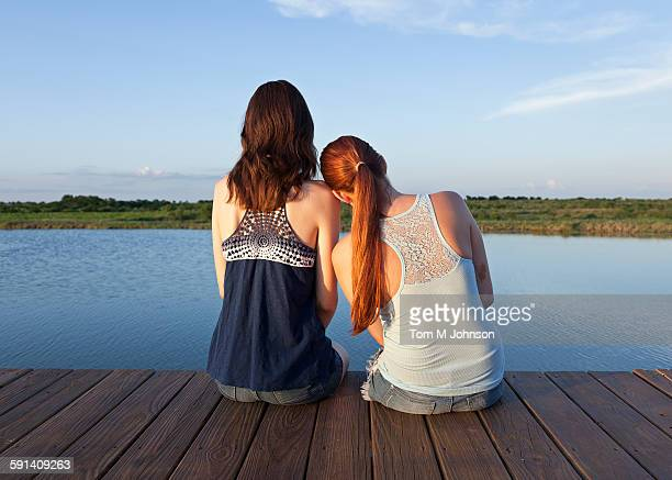 Caucasian women sitting on wooden dock over lake