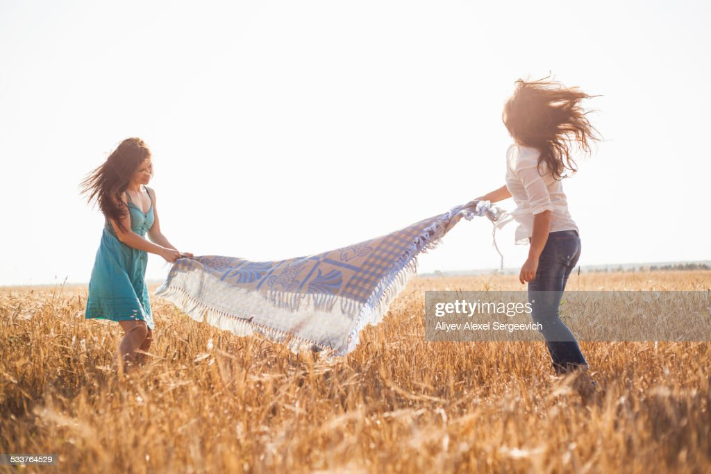 Caucasian women spreading blanket in rural field : Foto stock