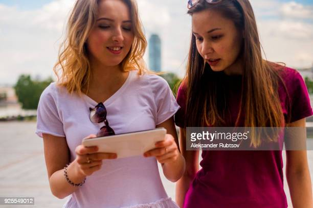 caucasian women using digital tablet outdoors - teen russia stock photos and pictures