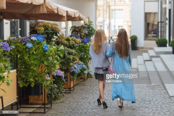Caucasian women walking arm in arm in cobblestone street
