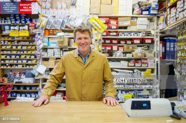 caucasian worker at cash register in hardware store - cash register stock pictures, royalty-free photos & images