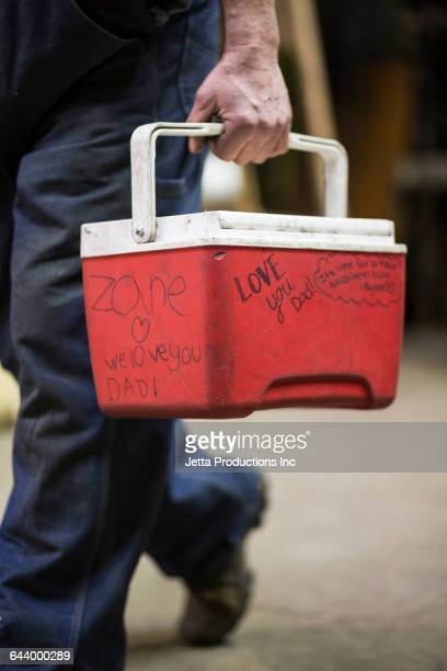 caucasian worker carrying cooler in factory - esky stock photos and pictures