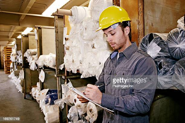 caucasian worker checking product in warehouse - industrial storage bins stock pictures, royalty-free photos & images