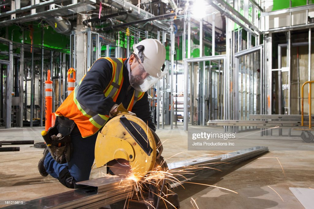 Caucasian worker cutting metal on site : Stock Photo