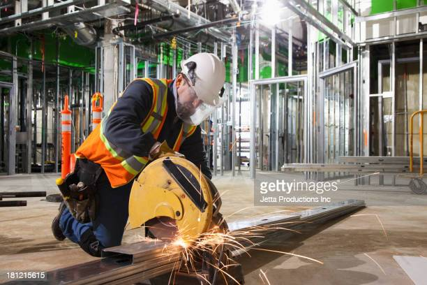 Caucasian worker cutting metal on site